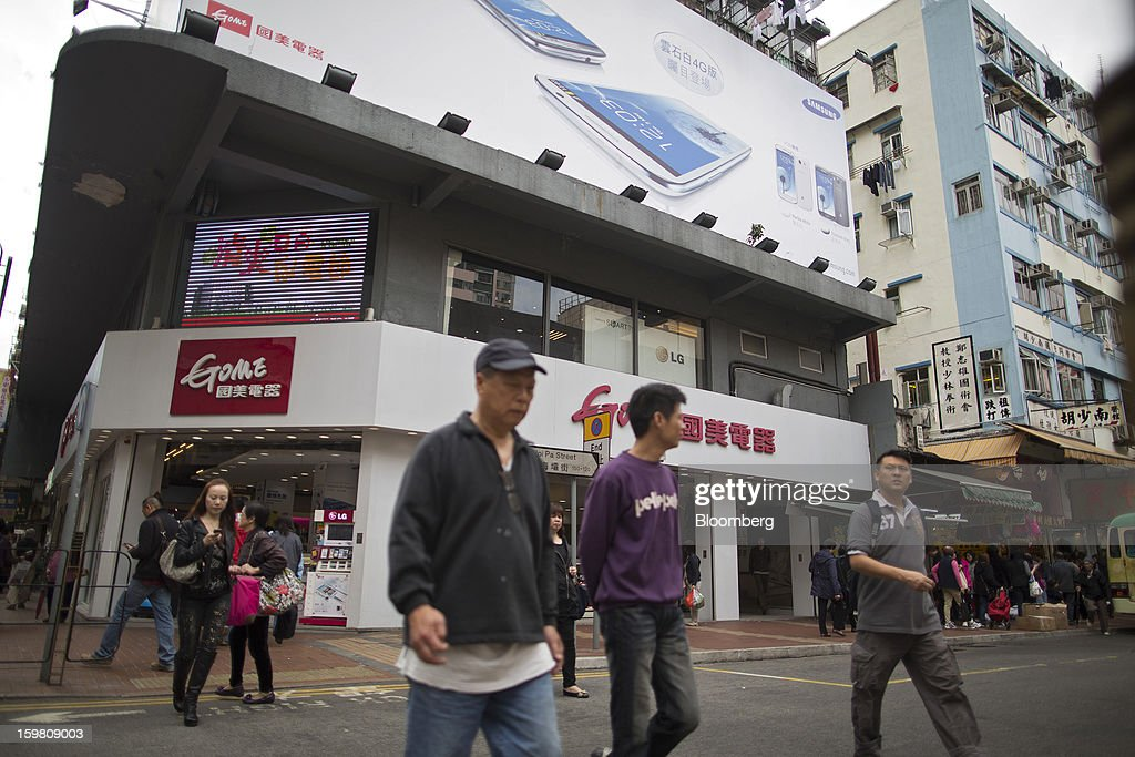 Pedestrians cross the road in front of a Gome-branded store in the district of Tsuen Wan in Hong Kong, China, on Monday, Jan. 21, 2012. Gome Electrical Appliances Holding Ltd.'s stocks tumbled in Hong Kong after the company confirmed a report it is closing Gome-branded stores in the city. Photographer: Jerome Favre/Bloomberg via Getty Images