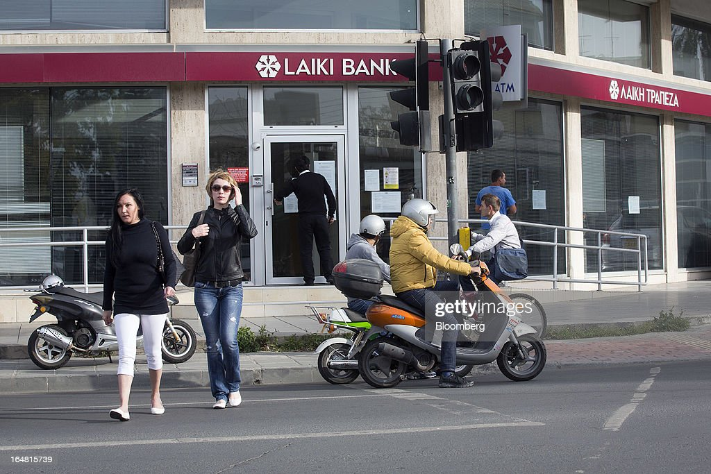 Pedestrians cross the road near a branch of Cyprus Popular Bank Pcl, also known as Laiki Bank, as banks open for the first time in two weeks in Nicosia, Cyprus, on Thursday, March 28, 2013. The Central Bank of Cyprus's capital controls will include a 300-euro ($383) daily limit on withdrawals and restrictions on transfers to accounts outside the country. Photographer: Simon Dawson/Bloomberg via Getty Images