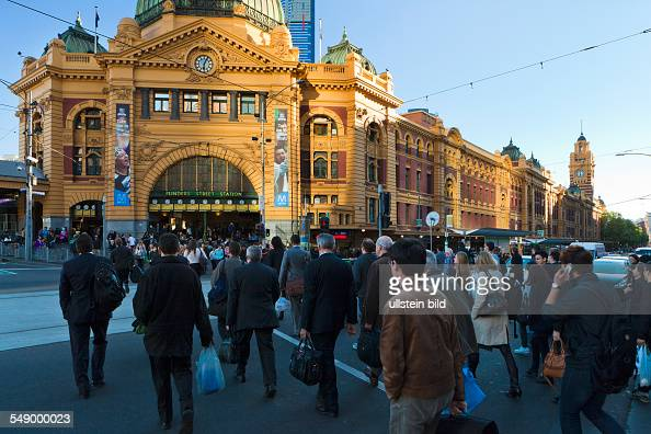 Pedestrians cross the street at Flinders Street Station