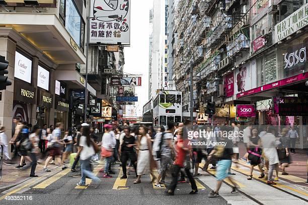Pedestrians cross the street at the Causeway Bay district of Hong Kong on October 19 2015 in Hong Kong China Key Hong Kong economic indicator drops...