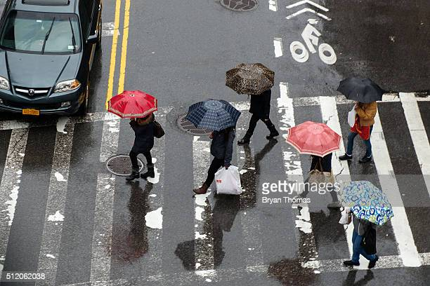 Pedestrians cross the street in Chinatown on February 24 2016 in New York City According to the National Weather Service as much as 15 inches of rain...