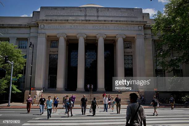 Pedestrians cross the street in front of the William Barton Rogers Building at the Massachusetts Institute of Technology campus in Cambridge...