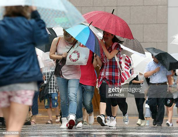 Pedestrians cross the street in heavy rain in Osaka on August 10 2014 Typhoon Halong slammed into western Japan making landfall on the Honshu main...