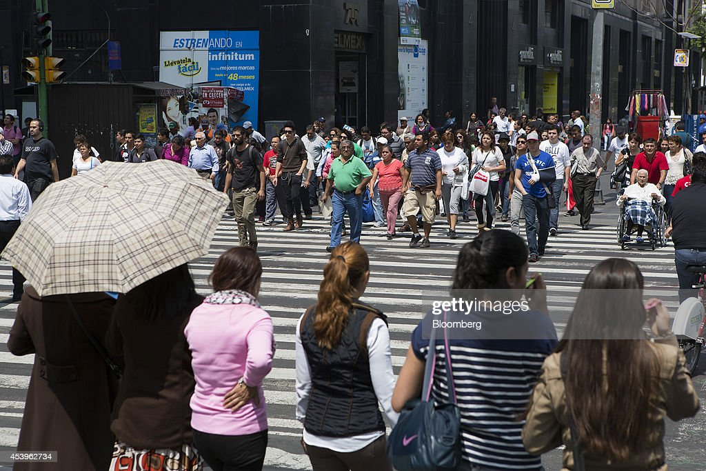 Pedestrians cross the street in Mexico City, Mexico, on Thursday, Aug. 21, 2014. Mexican consumer prices rose more than analysts expected in the first half of August and the unemployment rate rose to 5.47 percent in July compared with 4.8 percent in June. Photographer: Susana Gonzalez/Bloomberg via Getty Images