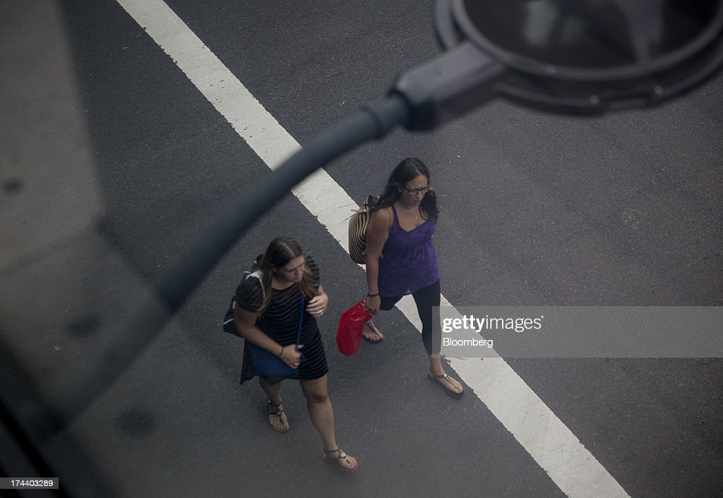 Pedestrians cross the street in New York, U.S., on Wednesday, July 24, 2013. The U.S. Conference Board is scheduled to release consumer confidence figures on July 30. Photographer: Scott Eells/Bloomberg via Getty Images