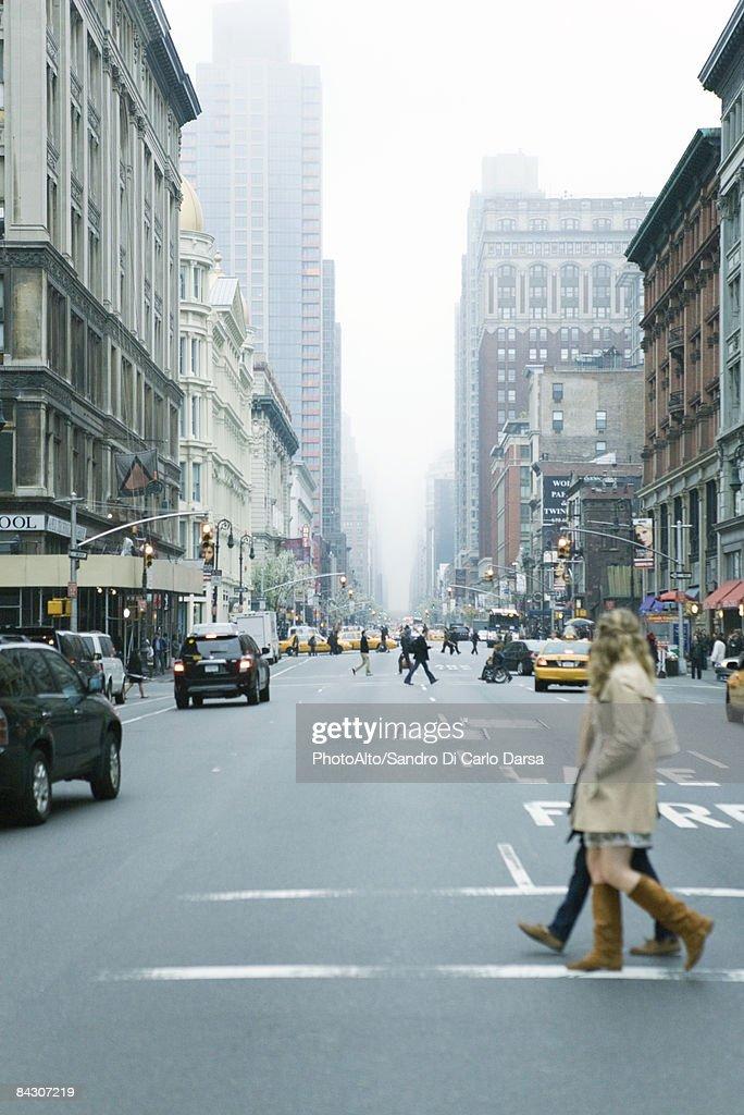 Pedestrians crossing street in crosswalk at W 19th Street and 6th Avenue Chelsea, New York, facing NE