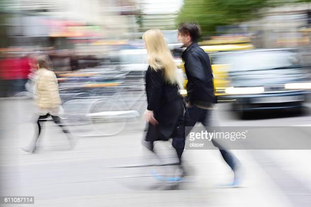 Pedestrians crossing street, motion and panning blur