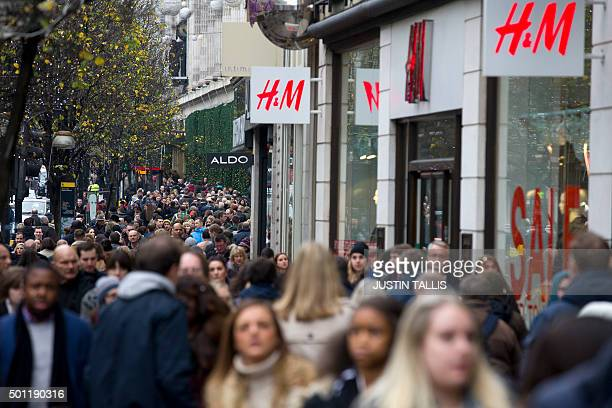 Pedestrians crowd Oxford Street one of the main shopping streets in central London on December 13 2015 less than two weeks before Christmas AFP PHOTO...