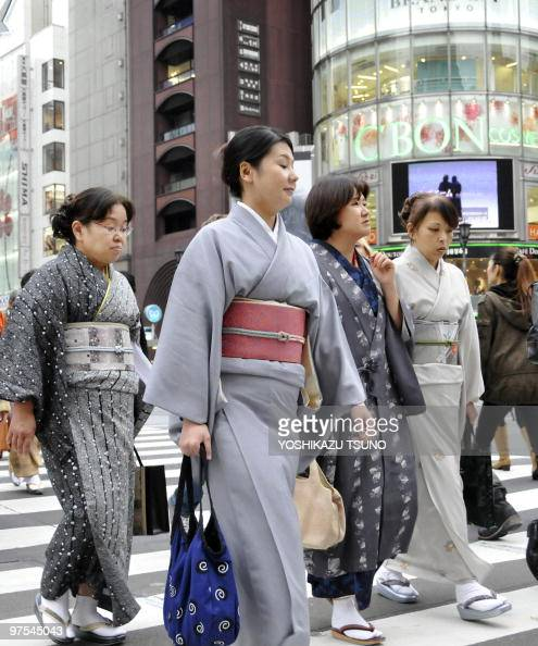 Pedestrians dressed in traditional kimonos cross a road at Tokyo's Ginza district on November 16 2009 Japan's economy grew at the fastest pace in two...