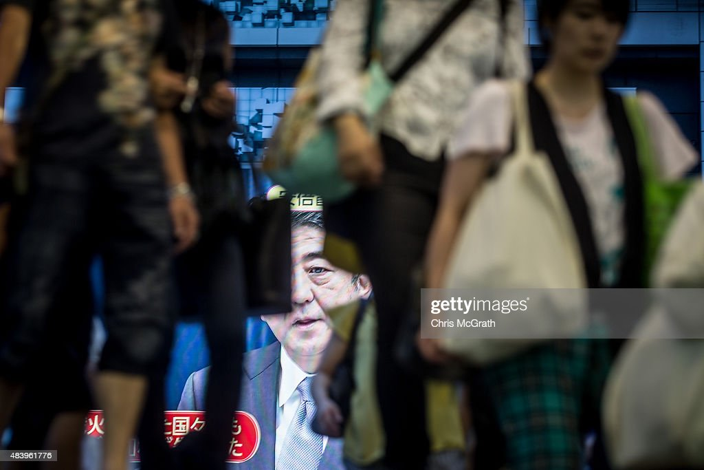 Pedestrians enter a train station in front of a big screen showing a live broadcast of Japanese Prime MinisterShinzo Abe as he delivers his WWII...