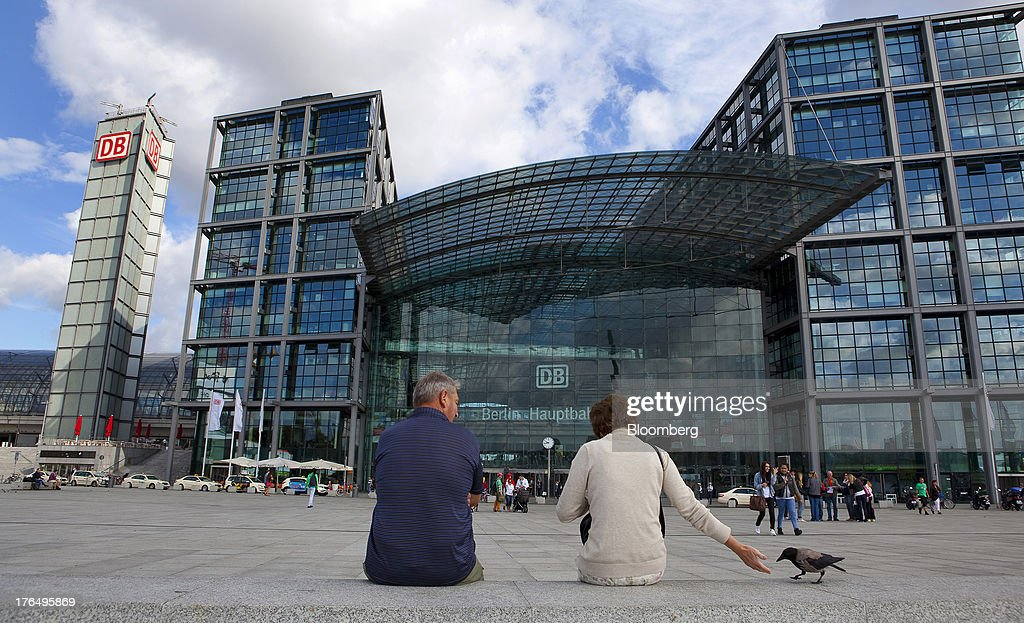 Pedestrians feed a bird as they sit outside Berlin Central Station, also known as Hauptbahnhof, in Berlin, Germany, on Tuesday, Aug. 13, 2013. German gross domestic product rose 0.7 percent from the first quarter and the French economy expanded 0.5 percent, the countries' national statistics offices said today. Photographer: Krisztian Bocsi/Bloomberg via Getty Images