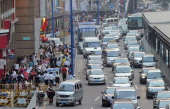 Pedestrians fill the pavement alongside heavily congested traffic in the town centre in Guangzhou in the southern Chinese province of Guangdong on...