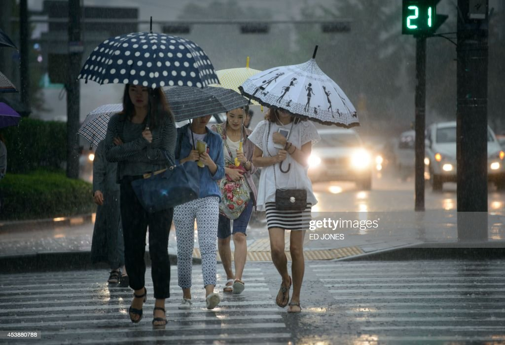 Pedestrians hold umbrellas as they cross a street in heavy rain in Seoul on August 21, 2014. AFP PHOTO / Ed Jones