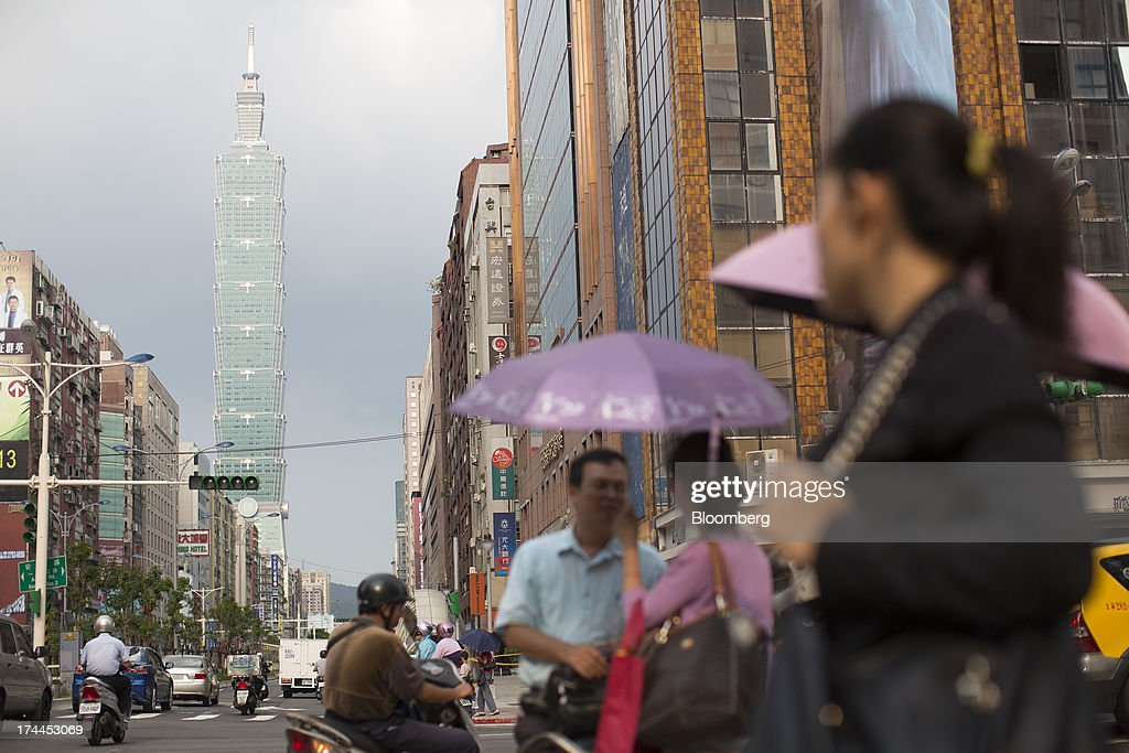 Pedestrians hold umbrellas while waiting for the green light at an intersection on Hsin Yi Road as the Taipei 101 building stands in the background in Taipei, Taiwan, on Wednesday, July 24, 2013.Taiwan President Ma Ying-jeou ruled out driving down the Taiwan dollar to boost exports following the currencys rally against the yen and said the government still aims for growth of at least 2 percent this year. Photographer: Jerome Favre/Bloomberg via Getty Images