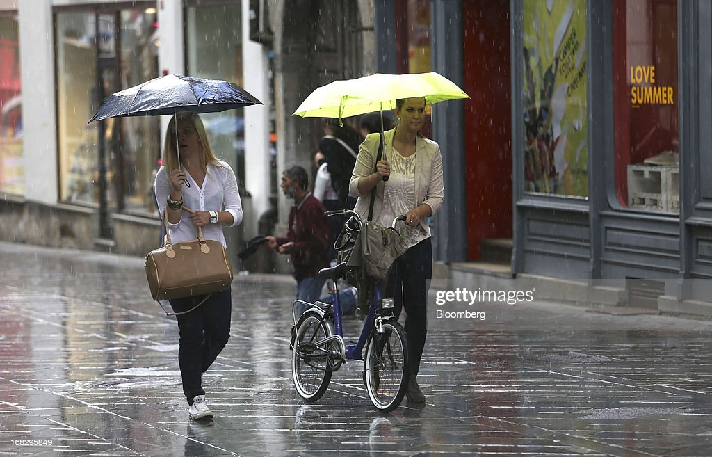 Pedestrians hold umbrellas while walking in the rain in Ljubljana, Slovenia, on Tuesday, May 7, 2013. Slovenia plans to increase taxes to make up for the swelling budget shortfall as the country works to recapitalize its banks. Photographer: Chris Ratcliffe/Bloomberg via Getty Images