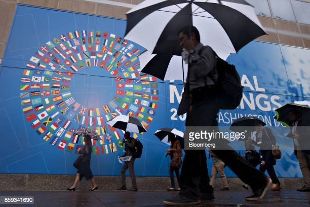 Pedestrians hold umbrellas while walking past a sign for the International Monetary Fund and World Bank Group Annual Meetings in Washington DC US on...