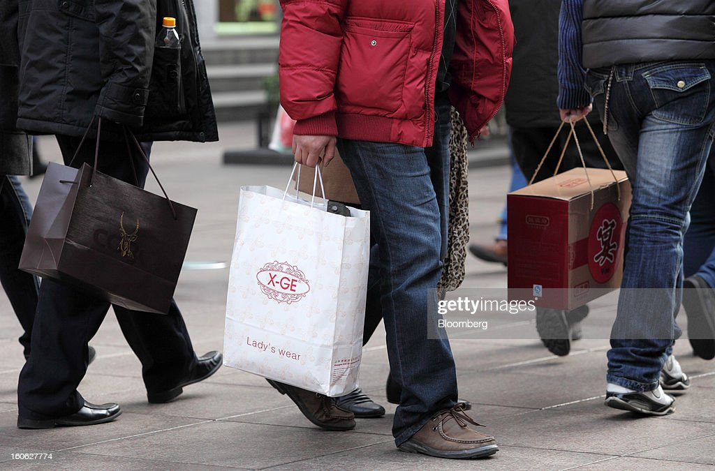 Pedestrians holding shopping bags walk through the East Nanjing Road shopping area of Shanghai, China, on Friday, Feb. 1, 2013. China's services industries grew at the fastest pace since August as gains in retailing and construction aid government efforts to drive a recovery in the world's second-biggest economy. Photographer: Tomohiro Ohsumi/Bloomberg via Getty Images