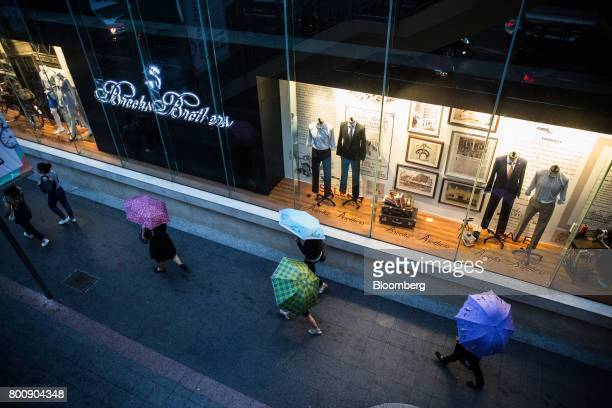 Pedestrians holding umbrellas walk past a Brooks Brothers Group Inc store at the Gaysorn Village shopping mall in Bangkok Thailand on Wednesday June...