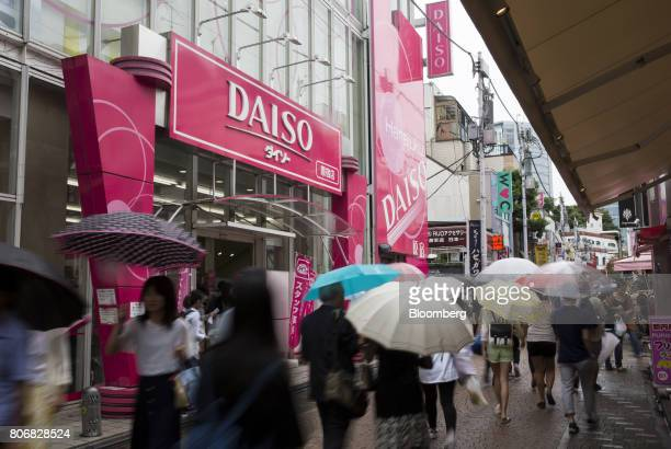 Pedestrians holding umbrellas walk past a Daiso store operated by Daiso Sangyo Corp in the Harajuku area of Tokyo Japan on Friday June 30 2017...