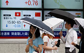 Pedestrians holding umbrellas walk past an electronic board displaying exchange rate of the yen against the Hong Kong dollar bottom left outside a...