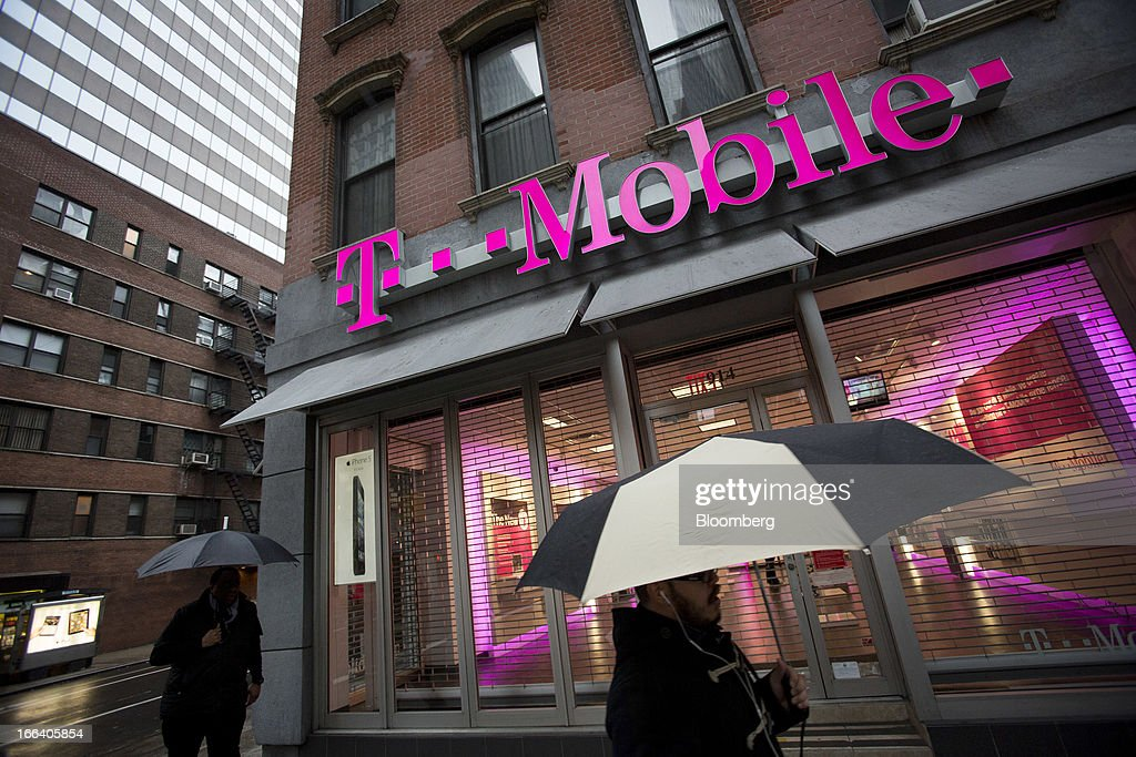 Pedestrians holding umbrellas walk through the rain past a T-Mobile USA Inc. retail location in New York, U.S., on Friday, April 12, 2013. T-Mobile USA Inc., the fourth-largest U.S. wireless carrier, will begin offering Apple Inc.'s iPhone for the first time today, providing the biggest showcase yet for its new installment-plan approach to selling phones. Photographer: Scott Eells/Bloomberg via Getty Images
