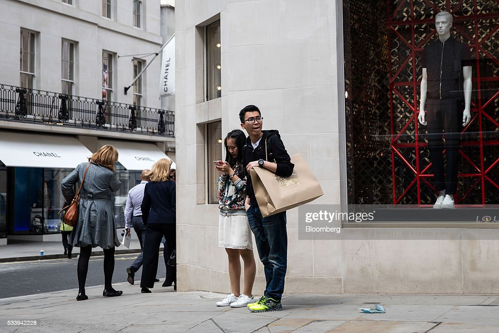 A pedestrians holds a Burberry Group Plc branded shopping bag while waiting to cross a road near the Chanel SA luxury goods store on New Bond Street in London, U.K., on Tuesday, May 24, 2016. U.K. retail sales began the second quarter with more momentum than economists forecast. Photographer: Simon Dawson/Bloomberg via Getty Images