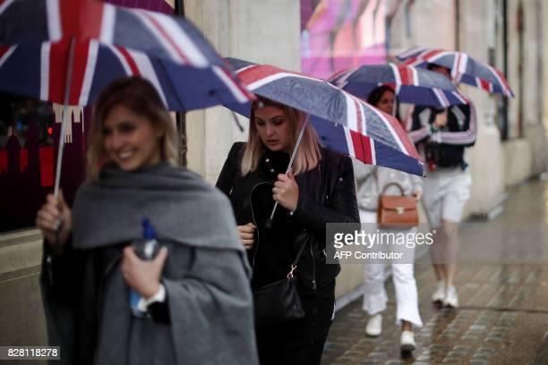 Pedestrians huddle under their umbrellas as rain fell in central London on August 9 2017 / AFP PHOTO / Tolga AKMEN