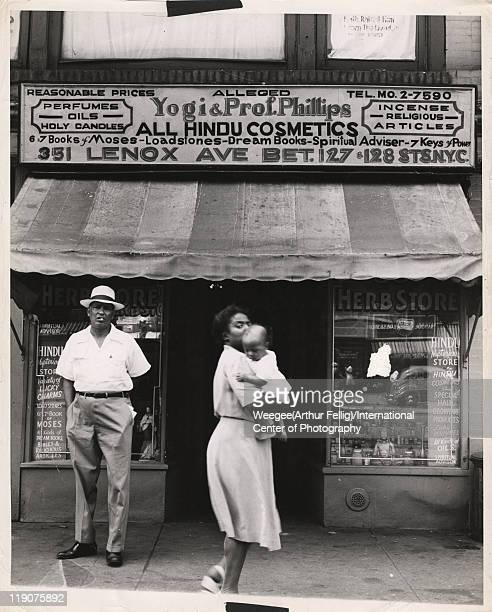 Pedestrians in front of an 'Herb Store' in Harlem which advertises a variety of cosmetics as well as books lodestones and religious articles New York...