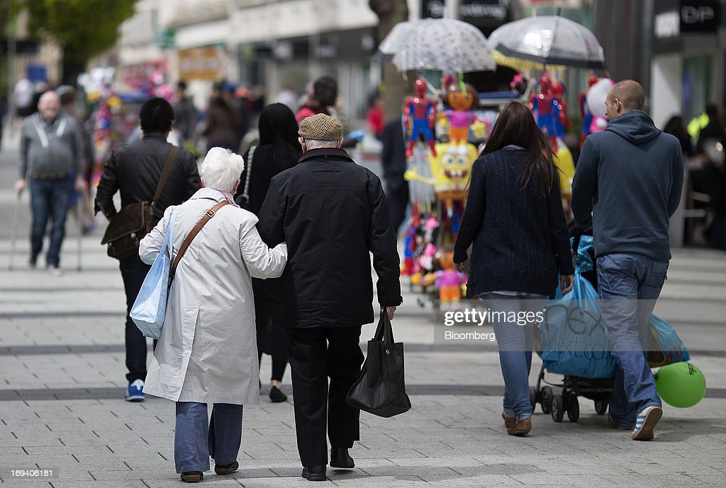 Pedestrians, including an elderly couple, walk pass street vendors in Cardiff, U.K. on Thursday, May 23, 2013. Bank of England Markets Director Paul Fisher said policy makers must continue to provide support to the British economy so that companies and consumers have room to reduce debts and rebuild confidence. Photographer: Simon Dawson/Bloomberg via Getty Images