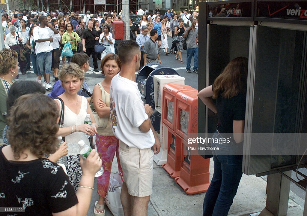 Pedestrians line up to use a pay phone as others stream down Broadway in Greenwich Village, New York City, Aug. 14, 2003. New York was hit by the largest power blackout in American history. More than 50 million people were affected by the outage, in Toronto, Detroit, Cleveland and New York City.