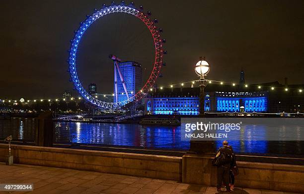 Pedestrians look accross the River Thames towards the London Eye illuminated in blue white and red lights resembling the colours of the French...