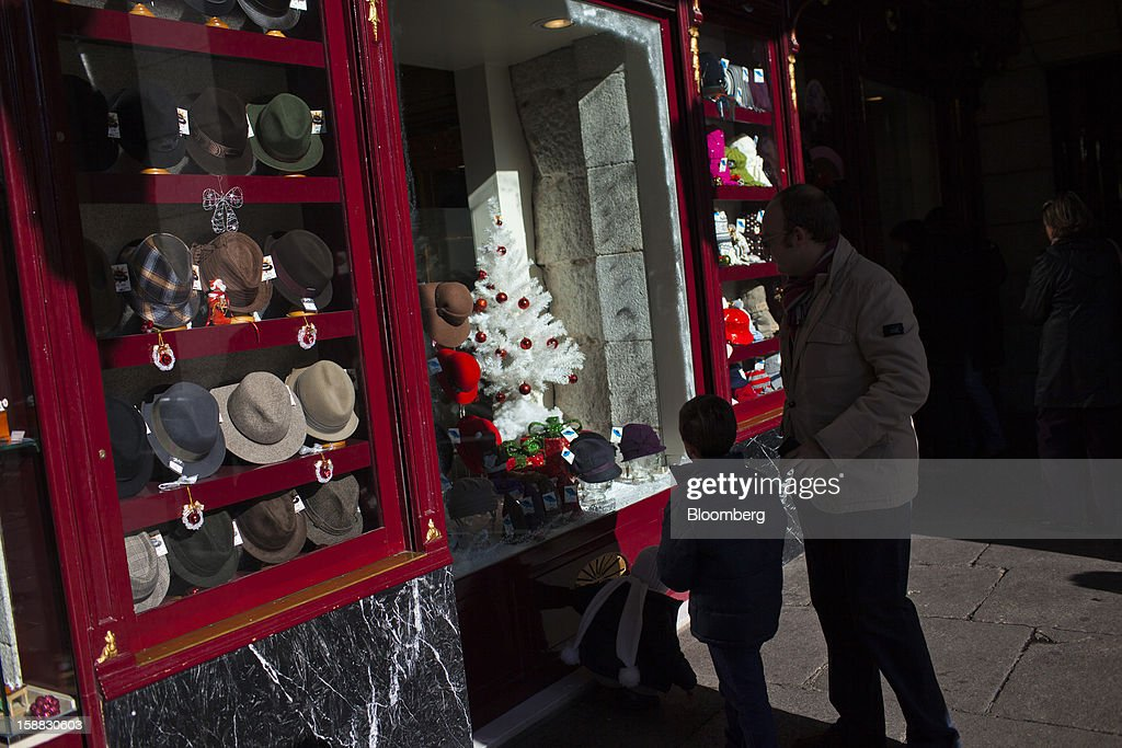 Pedestrians look at a Christmas display in the window of a hat store in Madrid, Spain, on Saturday, Dec. 29, 2012. Spain's economic activity kept falling in the fourth quarter, Bank of Spain says. Photographer: Angel Navarrete/Bloomberg via Getty Images