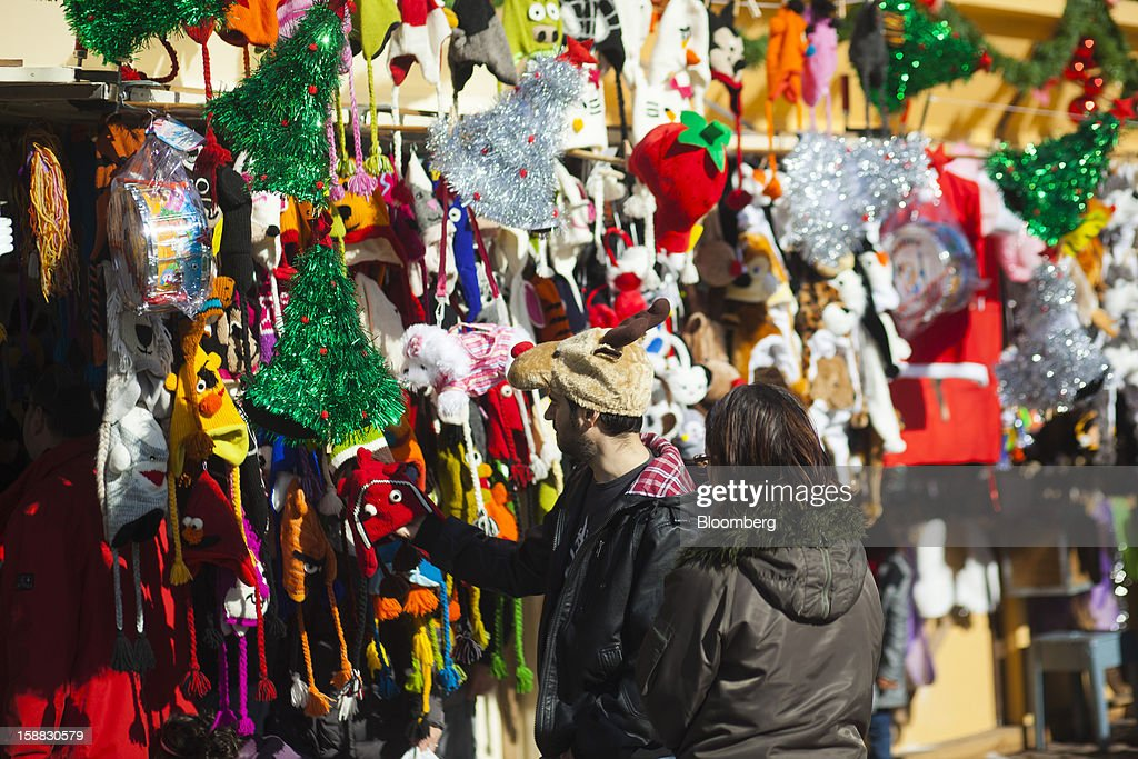 Pedestrians look at a display of comedy hats hanging from a display at a Christmas market in central Madrid, Spain, on Saturday, Dec. 29, 2012. Spain's economic activity kept falling in the fourth quarter, Bank of Spain says. Photographer: Angel Navarrete/Bloomberg via Getty Images