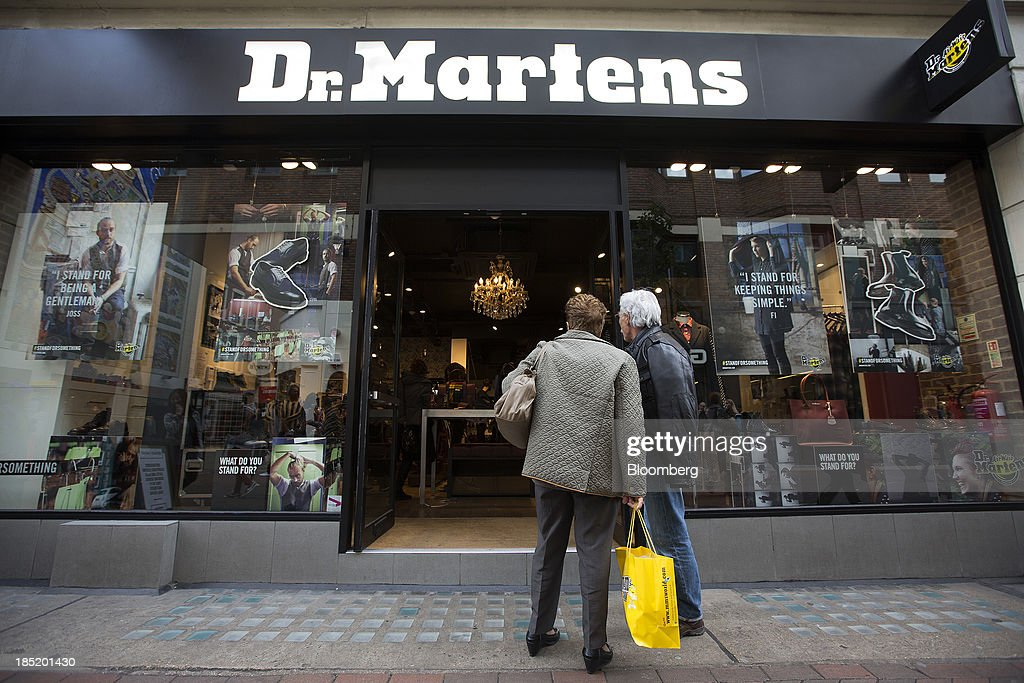 Pedestrians look at a display of footwear inside a Dr. Martens store in Convent Garden in London, U.K., on Friday, Oct. 18, 2013. Permira Advisers LLP, the London-based private-equity firm that owns clothing brand Hugo Boss, is in advanced talks to buy iconic British punk-boot maker Dr. Martens, said a person with knowledge of the negotiations. Photographer: Simon Dawson/Bloomberg via Getty Images