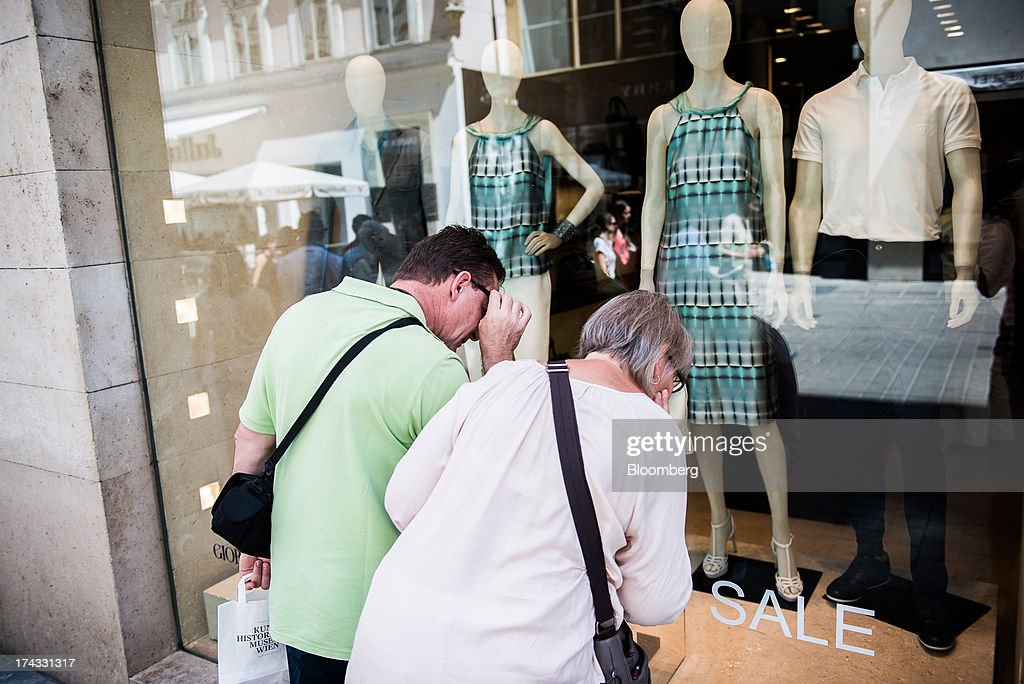 Pedestrians look at a sale sign in the window of a fashion store in Vienna, Austria, on Tuesday, July 23, 2013. Kommunalkredit Austria AG, the Austrian nationalized municipal lender, will have to wind down its loan book and close when that's complete after attempts to sell the bank failed, the European Commission said. Photographer: Akos Stiller/Bloomberg via Getty Images