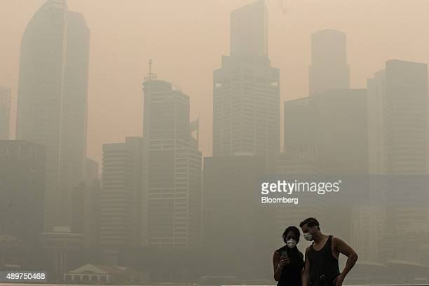 Pedestrians look at a smart device in the Marina Bay district as buildings in the central business district stand shrouded in smog in Singapore on...