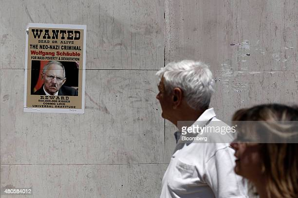 Pedestrians look at a 'Wanted Dead or Alive' poster depicting Wolfgang Schaeuble Germany's finance minister as a war criminal on a wall in Athens...