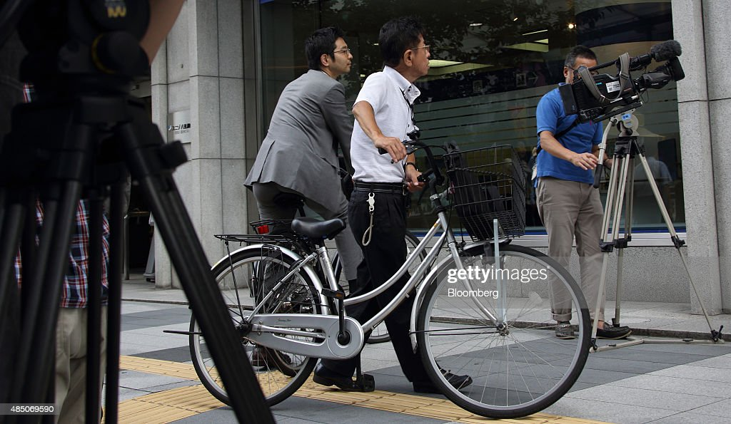 Pedestrians look at an electronic stock board displaying the closing figures of the Nikkei 225 Stock Average as members of the media operate their...