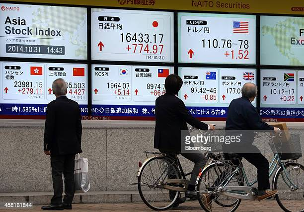 Pedestrians look at an electronic stock board displaying the figure of the Nikkei 225 Stock Average center top left and the exchange rate of the yen...