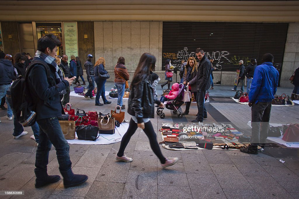 Pedestrians look at displays of goods for sale from street vendors in central Madrid, Spain, on Saturday, Dec. 29, 2012. Spain's economic activity kept falling in the fourth quarter, Bank of Spain says. Photographer: Angel Navarrete/Bloomberg via Getty Images