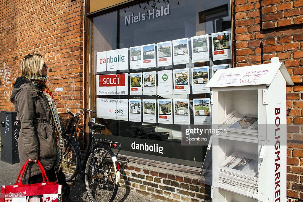 Pedestrians look at residential apartments and houses displayed for sale in the window display of an estate agent in Copenhagen, Denmark, on Thursday, March 28, 2013. Denmark's government rejected a plan by mortgage banks last week to split troubled loans and extend interest-only terms for amounts below an 80 percent loan-to-value limit. Photographer: Freya Ingrid Morales/Bloomberg via Getty Images