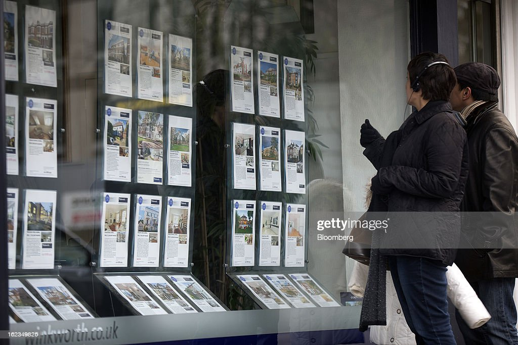 Pedestrians look at residential homes advertised in the window on an estate agent in the Putney district of London, U.K., on Friday, Feb. 22, 2013. U.K. home sellers raised their asking prices to the most for a February in five years as inquiries from potential buyers increased, Rightmove Plc said. Photographer: Simon Dawson/Bloomberg via Getty Images