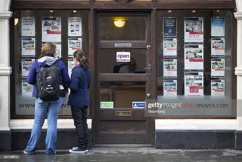 Pedestrians look at residential properties displayed for sale in the window of an estate agents in London, U.K., on Tuesday, Nov. 12, 2013. Under Bank of England Governor Mark Carney's forward-guidance policy, the central bank has pledged to not to withdraw stimulus at least until unemployment falls to 7 percent. Photographer: Simon Dawson/Bloomberg via Getty Images