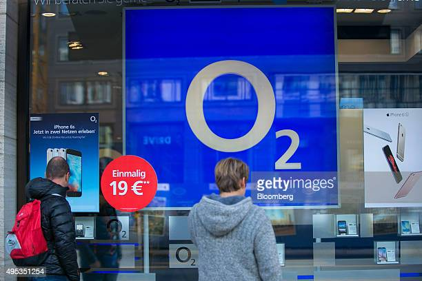 Pedestrians look at smartphones in the window of an O2 mobile phone store operated by Telefonica Deutschland Holding AG in Berlin Germany on Monday...