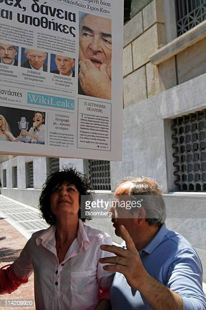 Pedestrians look at the Dominique StraussKahn headlines on a newspaper hanging from a kiosk in Athens Greece on Monday May 16 2011 International...