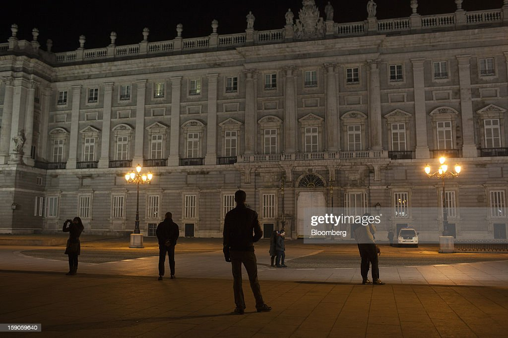 Pedestrians look at the facade of the Royal palace, illuminated by street lights, at night in Madrid, Spain, on Sunday, Jan. 6, 2013. In December, the Spanish parliament passed an energy law that imposed a 7 percent tax on electricity generation from Jan. 1 to plug the deficit. Photographer: Angel Navarrete/Bloomberg via Getty Images