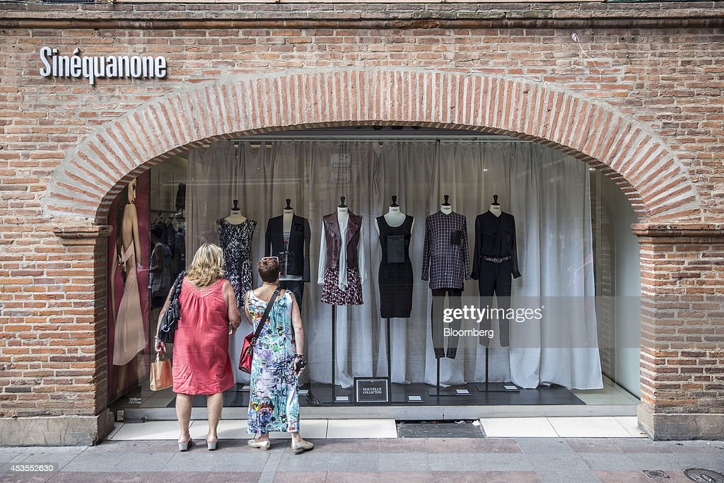 Pedestrians look at the window display of a Sinequanone women's clothing fashion store in Toulouse, France, on Tuesday, Aug. 12, 2014. The euro traded 0.3 percent from a nine-month low before reports this week that may show growth in the region weakened and inflation slowed, adding to signs the bloc's economy is struggling to recover. Photographer: Balint Porneczi/Bloomberg via Getty Images