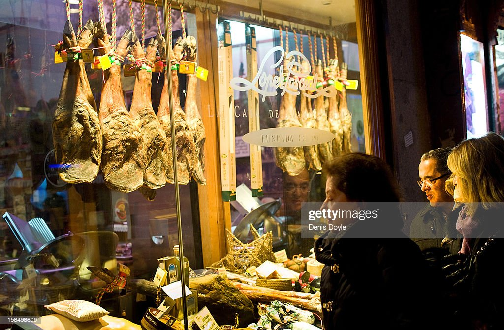 Pedestrians look at the window display of the Alberto Lopez Araque jamon Iberico shop on December 14, 2012 in Madrid, Spain. Dry-cured Iberian ham or Jamon Iberico is a favourite amongst Spaniards and producers are hoping for improved sales over the busy christmas period. The jamon Iberico de Bellota are usually dry-cured for up to three years after the pigs have been few on a diet of acorns in the last three months of their lives.