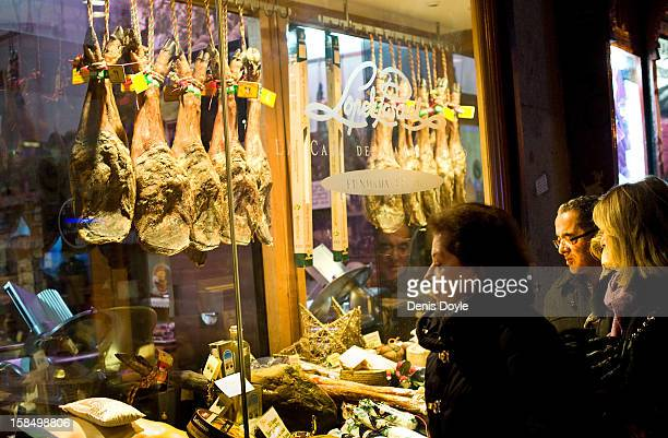 Pedestrians look at the window display of the Alberto Lopez Araque jamon Iberico shop on December 14 2012 in Madrid Spain Drycured Iberian ham or...
