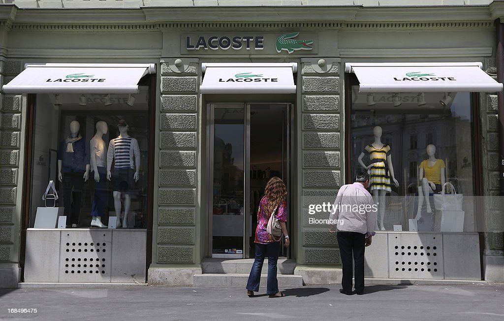 Pedestrians look at the window displays of a Lacoste SA clothing store in Ljubljana, Slovenia, on Thursday, May 9, 2013. The Adriatic nation is seeking to fix its ailing lenders with a cash injection of at least 900 million euros ($1.17 billion) after Cyprus's bailout focused investors on countries with weak banking industries. Photographer: Chris Ratcliffe/Bloomberg via Getty Images